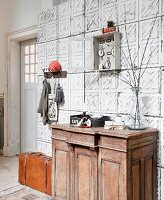 Antique, rustic cabinet against foyer wall clad in moulded tiles