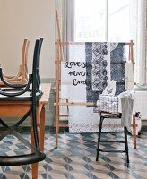 Chairs upturned on table and bar stool in front of fabric on clothes horse below window