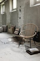 Shell chair made from curved rattan on black metal frame next to animal-skin rug in industrial, unrenovated interior