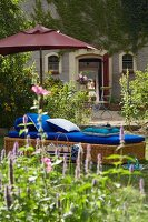 A parasol and a wicker lounger with blue cushions in a garden with a vine-covered facade of a French country house in the background