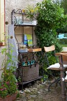 An ornate iron shelf with kitchen utensils and an antique table with garden chairs on a paved area in a garden