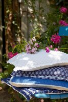 A stack of cushions with various blue and white covers and phlox flowers on a chair in a garden