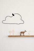 Deer figurine and cut-out paper trees on narrow floating shelf below hand-crafted wire cloud stuck to wall with washi tape