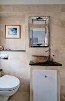 Masonry washstand with stone basin and toilet in elegant bathroom with sandstone tiles