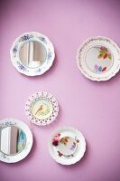 Colourful painted plates, some with mirrored centres, hung on lilac wall