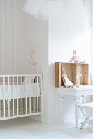 White-painted cot and rabbit soft toys on table in nursery with pale, striped wallpaper