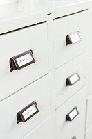 Labelled drawer handles on white-painted, vintage chest of drawers