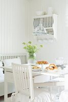 Table set for afternoon coffee with home-made pastries and jar of wildflowers in white, shabby-chic kitchen with old-fashioned plate rack on wall