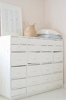 Cushions, rattan bag and picture on old, white-painted chest of drawers with shell handles