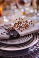 Festive place setting with linen napkin and golden twig
