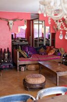 Eclectic style; comfortable living room with many cushions on wooden couch, mirror shaped like step pyramid, hunting trophy and pink wall