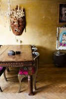 Hand-crafted Oriental wooden mask on gold wall, chandelier and carved exotic-wood table in eclectic interior