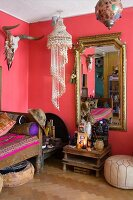 Pink living area with hunting trophy, decorative pendant lamp, altar with Buddha figurines and gilt-framed mirror