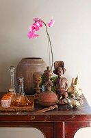 Ethnic, wooden figurines next to glass carafes and beakers on tray and pink orchid on console table
