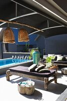 Rustic wooden benches with seat cushions on sunny terrace with dark fabric awning and pool in background