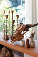 Animal skull next to collection of metal candlesticks on wooden surface