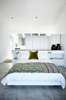 Bedroom with double bed, ethnic bedspread, sideboard and dressing area in background