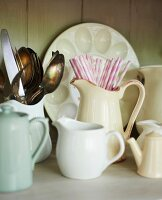 White vintage china jugs, some containing cutlery and drinking straws