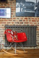 Classic red rocking chair and grey-painted radiator below pictures on brick wall