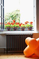 Orange 70s floor lamp below open window and potted red geraniums on windowsill