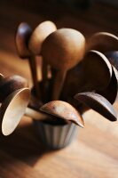 Several vintage wooden spoons in pot on wooden surface