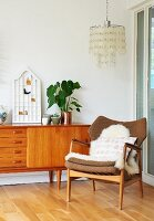 Sheepskin rug on fifties-style armchair, partially visible sideboard and ceiling lamp with lampshade made from circular pendants in corner