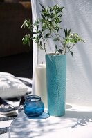 Olive branch in turquoise vase, glass tealight holders and large pillar candle