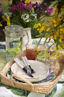 Glasses, jug of water and plates on basket tray outdoors