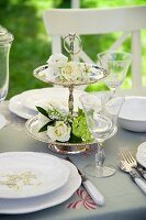 Silver cake stand decorated with white flowers on table set for wedding
