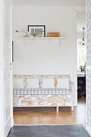 View through open door of shabby-chic bench and picture on white bracket shelf