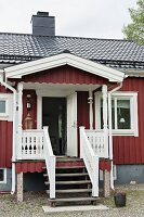 Traditional Swedish house with steps leading to porch and open front door