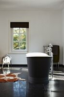 Free-standing vintage bathtub, standpipe tap fittings, large black floor tiles and cowhide rug in minimalist bathroom