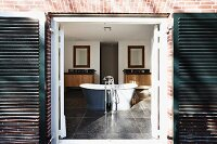 View through open door with dark shutters into spacious bathroom with freestanding bathtub and standpipe bath tap fittings