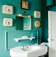 Five clocks surrounding mirror above sink, Marcillat-Encombraille, France