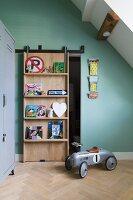 Sliding door with integrated shelves in child's attic bedroom