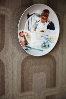 Decorative wall plate with photo motif on retro-patterned wallpaper