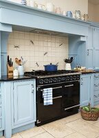 Vintage, black gas cooker under mantel hood flanked by country-house-style kitchen cabinets painted pale blue