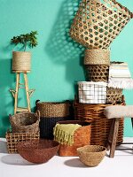 Plant pots and baskets in various woven materials against turquoise wall