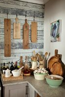 Nostalgic bowls and cooking utensils on corner worksurface under chopping boards hung on wall