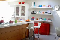 Island counter and white bar stools in open-plan kitchen with colourful crockery on white floating shelves above red chest of drawers