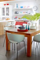 White shell chairs around wooden table in front of modern kitchen counter with bar stools and floating shelves