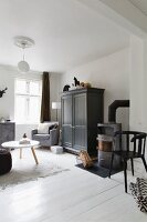 Corner of monochrome living room; coffee table with white top and cupboard painted dark grey on white wooden floor