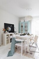 White dining area with modern chairs around wooden table and pastel display cabinet in background