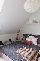 Double bed with blanket and arranged scatter cushions below sloping ceiling