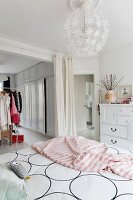 Bed linen with graphic pattern and pink blanket on feminine bed and spherical pendant lamp in bedroom