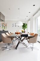 Elegant swivel chairs with pale upholstery around modern table with stainless steel frame