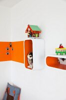 Shelving modules with orange interior surfaces on wall next to orange stripe in nursery