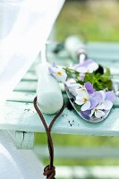 Violas lying on garden trowel on garden chair
