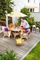 Comfortable seating area with wicker furniture below parasol and woman on DIY wooden terrace