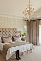 Double bed with scatter cushions and button-tufted headboard in traditional bedroom with brocade wallpaper and elegant chandelier